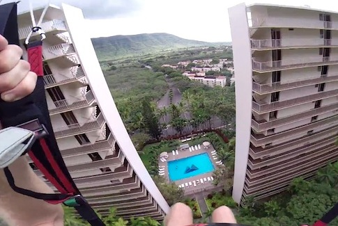 Crazy Paraglider Swoops Down Between Two Buildings In Hawaii